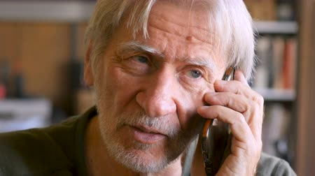 семидесятые годы : Handsome aging senior man talking on smart phone mobile device in his house - dolly shot