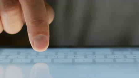 touchpad : Extreme close up of finger typing on touchscreen keyboard digital tablet