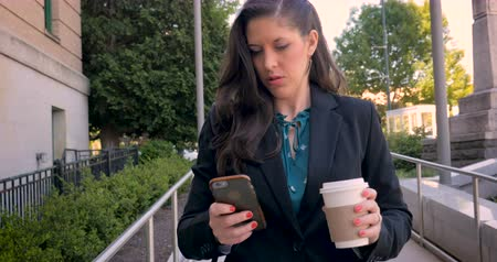 executivo : Attractive professional millennial businesswoman or lawyer on mobile phone technology walking on walkway with briefcase and to go coffee cup in 4k stabilized shot