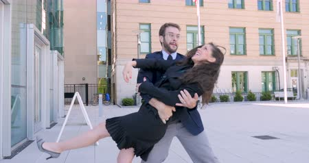 parceiro : A excited beautiful woman business executive and handsome millennial businessman with a beard high five and dancing celebrating victory and success for their achievements outside an office building Stock Footage