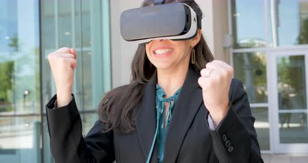 valóság : Successful happy woman wearing business clothing celebrating while working outside an office building in virtual reality with VR headset in 4k Stock mozgókép