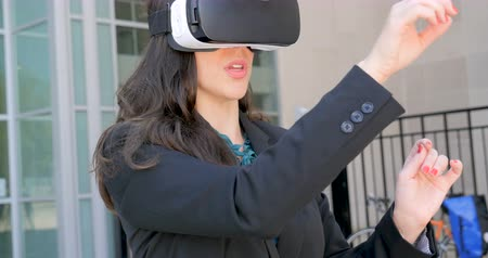 fejhallgató : An attractive female business executive virtual reality working with her VR headset outside a modern glass office building in 4k medium shot