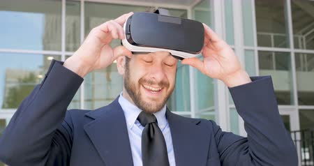 executivo : Handsome millennial businessman leaves his virtual reality world removing her VR headset and is happy and excited in the real world in 4k