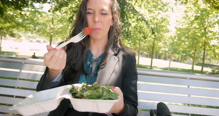 descanso : Young pretty millennial 30s woman eating healthy salad with leafy greens and organic strawberries in biodegradable takeaway lunch container outside in 4k hand held Stock Footage