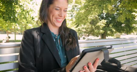executivo : Attractive woman remembering something and laughing while outside on digital tablet technology hand held in 4k