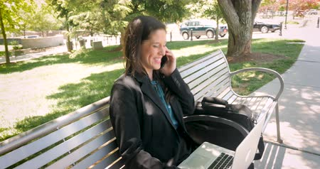 executivo : Successful corporate executive millennial businesswoman in her 30s working on her laptop computer and talking on her mobile phone dolly shot in 4k