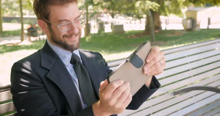 concentrando : Handsome man in his 30s with beard and eyeglasses taking a break from work playing video game on his digital tablet outside dolly shot 4k