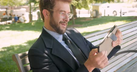 concentrando : Handsome smiling happy millennial businessman in his 30s playing video game driving or flying simulator on digital tablet outside on park bench in 4k