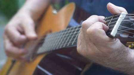 enstrüman : Close up of senior man playing chords and finger picking music songs on acoustic guitar Stok Video