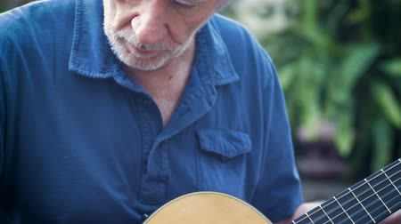 gitáros : Attractive healthy aging senior man playing acoustic guitar outside in his garden tilt up