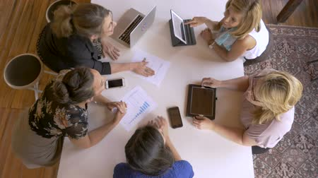 diversidade : Group of diverse pretty young millennial women in business on laptop, cell phones and tablets discussing charts and graphs during meeting in slow motion overhead shot Vídeos