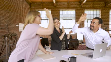corporativa : Diverse group of creative business team members celebrating with high fives at a startup in a modern office setting in slow motion