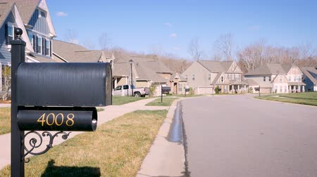 entrada da garagem : Generic suburban neighborhood during the winter day with a mailbox and bare trees blowing in the wind establishing shot