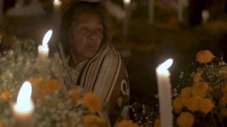 família : CUCUCHUCHO, MEXICO - NOVEMBER 1, 2016 - Old indigenous woman celebrating Day of the Dead at a graveyard alter at night wrapped in a blanket near Patzcuaro, Michoacan
