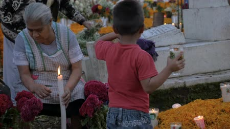 запомнить : TZURUMUTARO, MEXICO - NOVEMBER 1, 2016 - Little Mexican boy helping his mother and grandmother at Day of the Dead