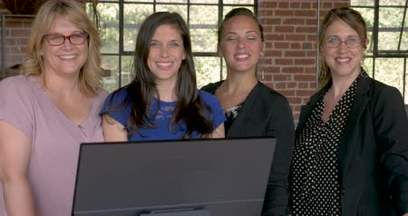 trabalho em equipe : Portrait of four attractive successful professional entrepreneur women smiling behind a computer monitor in modern startup office - dolly shot Vídeos
