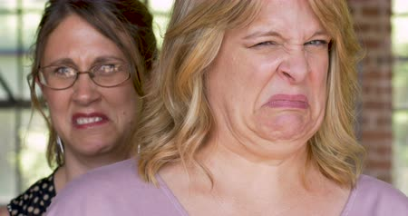 unpleasant smell : Two women expressing disgust and disapproval with negative facial expressions for something Stock Footage