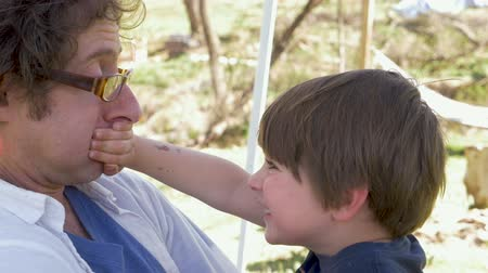 bonding : Laughing handsome young 4 year old boy holding his fathers mouth closed outside during the spring in the daytime