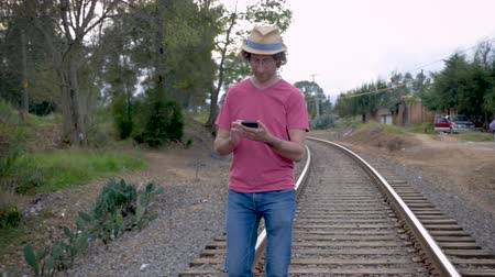 chapéu : Man wearing a hat walking on railroad tracks while looking down at and using his smart phone in slow motion