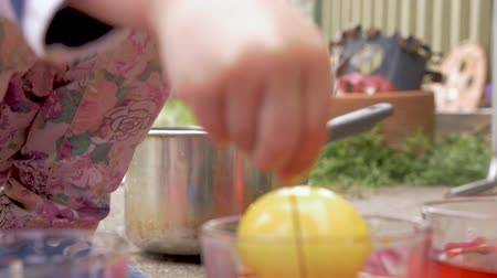 volný čas : Close up of two young children coloring and dyeing easter eggs together outside in slow motion