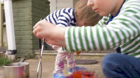 festividades : Two young children painting and dyeing easter eggs together outside in slow motion