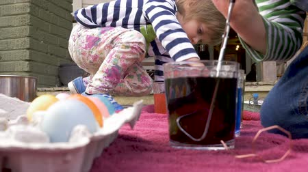 volný čas : Low angle of two siblings painting easter eggs together in colored dye in slow motion outside for the holiday celebration Dostupné videozáznamy
