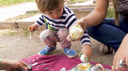 festividades : Cute young boy and girl coloring easter eggs and making a mess with their mom in slow motion outside