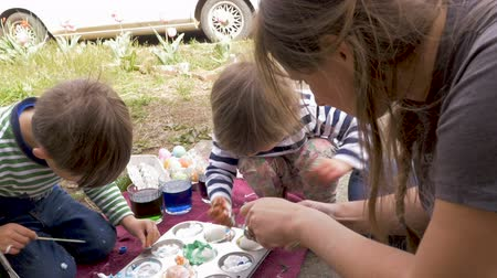 tradição : Family with a mom, a young boy and girl working on an arts and crafts project together outside in slow motion