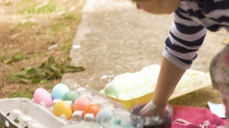 festividades : Cute young 3 year old girl grabbing a colored easter egg with her hand outside in slow motion