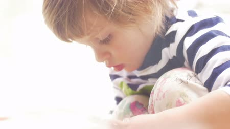 zajímavý : Dreamy moment of a cute little girl concentrating on playing in slow motion