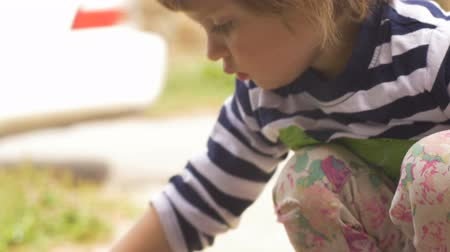фокус : Intimate moment with a cute little girl focused on playing outside hand held slow motion