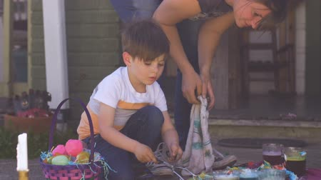 festividades : Millennial mother and young son coloring and dyeing easter eggs together outside in slow motion Stock Footage