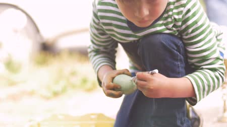 ajoelhado : Little boy kneeling and coloring an easter egg with a crayon in slow motion outside for the holiday Vídeos