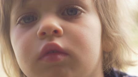 assustado : Beautiful innocent concerned worried shy little girl looking at the camera in slow motion Vídeos