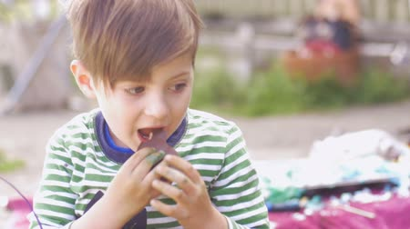 festividades : Adorable happy little boy eating chocolate and nodding his head outside in slow motion