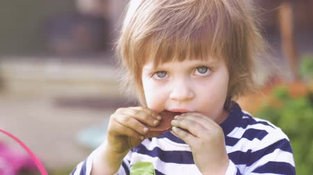 festividades : Cute little young girl taking a bite out of some candy chocolate outside in slow motion Stock Footage