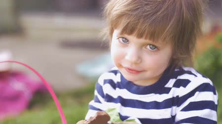 festividades : Adorable little girl enjoying chocolate smiling and looking at the camera outside in slow motion
