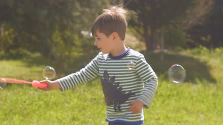infantil : Adorable little boy spinning in circles making bubbles outside in a park on a lawn in slow motion