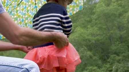 suçsuzluk : A man helps his daughter holding an umbrella get dressed pulling up her skirt outside looking up towards the trees in slow motion