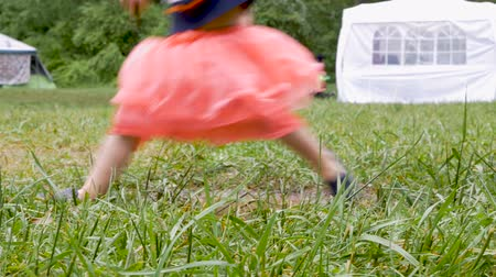avoiding : Close up low angle of a young toddler girl jumping over a puddle in the grass at a festival in slow motion Stock Footage