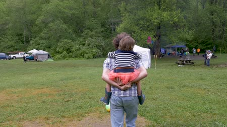 реальное время : Man carrying a young little girl on his back walking away from the camera at a festival event outside in slow motion