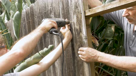 parafusos : A mature father in his 70s and middle aged son work together using an electric drill to screw fence boards into a post