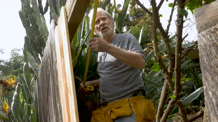 trabalhador manual : Low angle of a senior adult man in his 70s measuring wood for a repair of a broken fence outside in his yard Vídeos