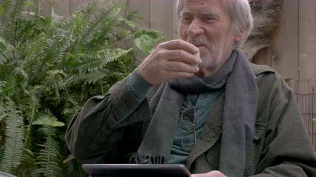 семидесятые годы : Candid moment of a healthy attractive senior man in his 70s laughing and drinking sake with a tablet sitting outside