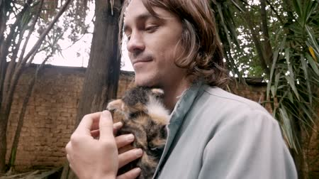 upřímný : Attractive young millennial man in his 20s holding a tiny kitten against his chest in slow motion Dostupné videozáznamy