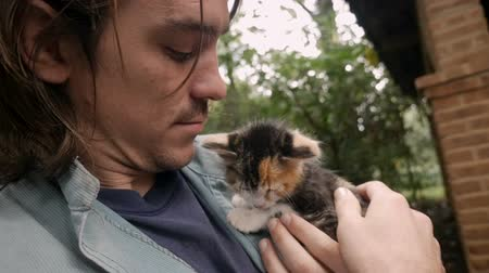 companionship : Handsome man holding a baby calico cat close to his face gently petting her outside in slow motion Stock Footage