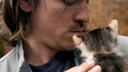 companionship : Portrait of a man holding a young calico kitten near his face in slow motion Stock Footage