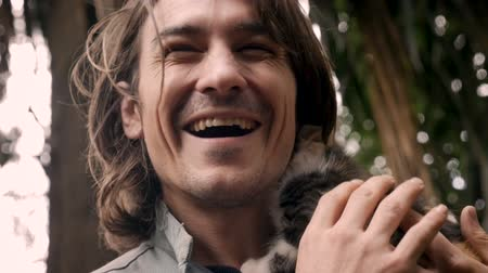 łaskotanie : Happy smiling and laughing attractive man holding a tiny kitten near his face in slow motion Wideo