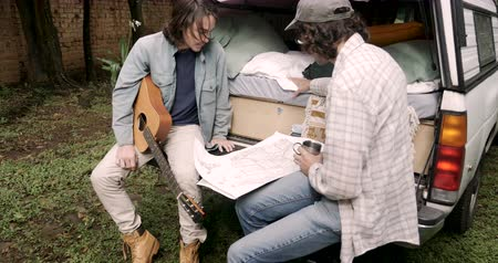 интимный : Two attractive hipster best male friends sitting on the tailgate of their small pickup looking at a paper map talking about where to travel next Стоковые видеозаписи