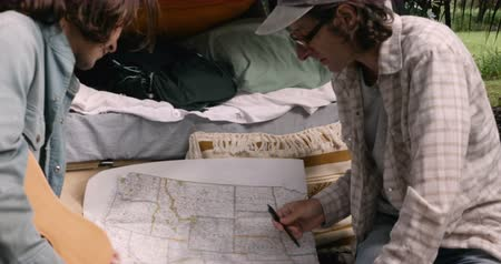 интимный : Two men planning their road trip in the USA looking and pointing at a paper map while sitting on a tailgate